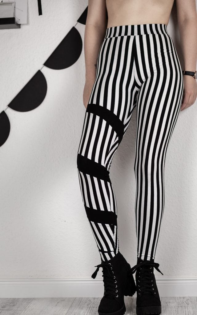 Version B der Leggings aus schwarz-weiß gestreiftem Jersey mit einem normalen Bein und einem Bein mit Swirl